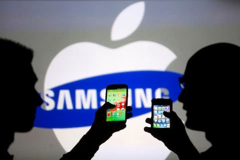 Men pose with Samsung Galaxy S3 and iPhone 4 smartphones in photo illustration in Zenica