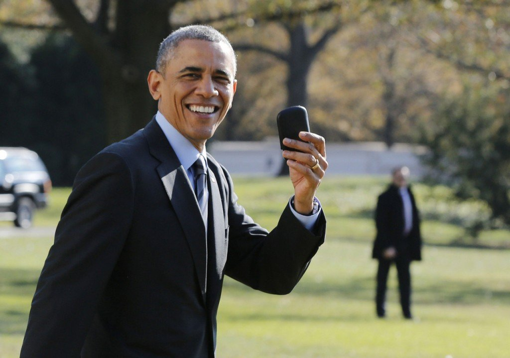 U.S. President Obama holds up his BlackBerry device after he returned inside the White House to retrieve it, after boarding Marine One on the South Lawn of the White House in Washington