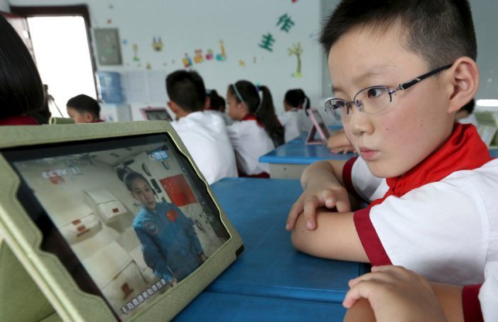 A student looks at his iPad as his class watches a live broadcast of a lecture given by Shenzhou-10 spacecraft astronauts on the Tiangong-1 space module, at a primary school in Quzhou