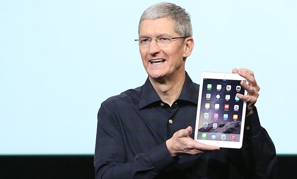 Apple CEO Tim Cook holds an iPad during a presentation at Apple headquarters in Cupertino, California October 16, 2014. REUTERS/Robert Galbraith (UNITED STATES - Tags: SCIENCE TECHNOLOGY BUSINESS) - RTR4AGWE