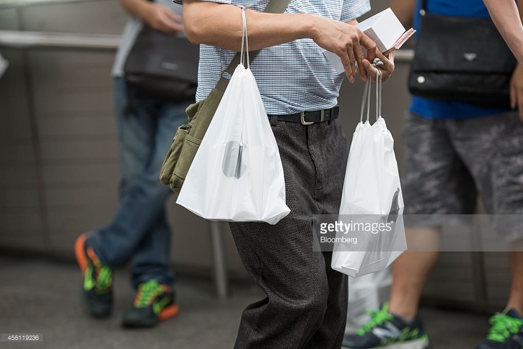 A man holds plastic bags containing boxed Apple Inc. iPhones 6 and 6 Plus and Hong Kong dollar bills as he tries to resell the devices outside the company's Central district store in Hong Kong, China, on Friday, Sept. 26, 2014. Photographer: Jerome Favre/Bloomberg